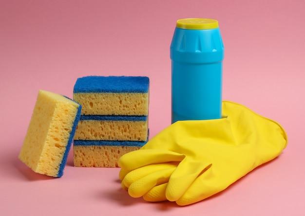 クリーニングのコンセプト。ピンクのパステルカラーの背景に洗剤ボトル、スポンジ、手袋