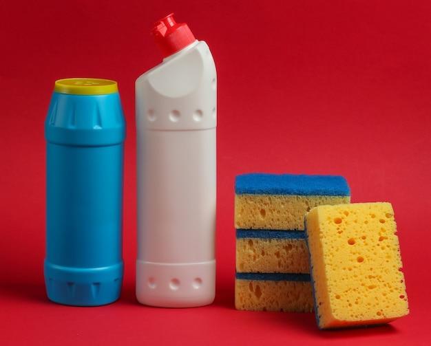 クリーニングのコンセプト。洗剤のボトル、赤い背景のスポンジ