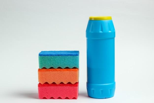 Концепция очистки. бутылки для моющих средств, губки на белом фоне