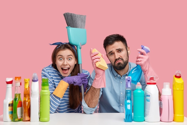 Concetto di pulizia. il giovane triste tiene il detergente e la spugna, ha un'espressione infelice, stufo dello specchio del bucato, signora allegra indica il ragazzo, porta la spazzola