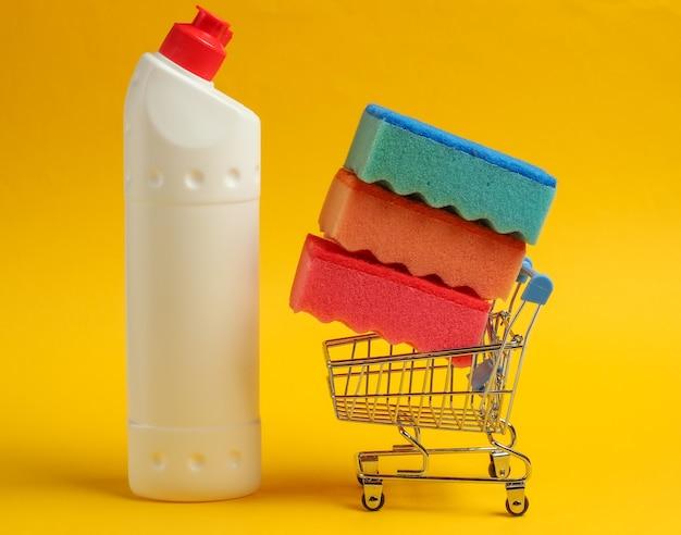 Концепция очистки. тележка для покупок с бутылкой моющего средства, губки на желтом фоне