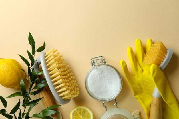 ベージュの孤立した背景に環境に優しいクリーニングツールとレモンを使用したクリーニングの概念