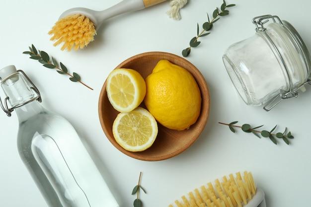 白い孤立した背景に環境に優しいクリーニングツールとレモンを使用したクリーニングコンセプト