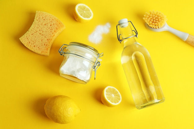 Cleaning concept with eco friendly cleaning tools and lemons on yellow isolated background