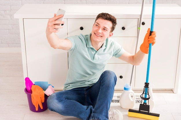 Cleaning concept with man holding smartphone