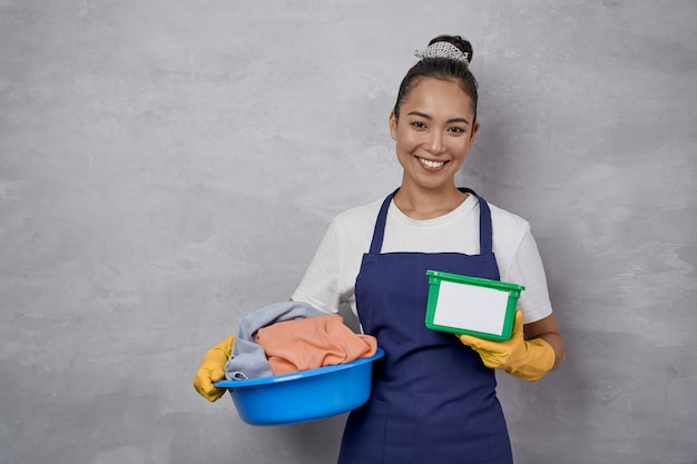 Cleaning day. portrait of happy housewife or maid woman in uniform holding basin full of dirty clothes and green plastic box with washing capsules, standing against grey wall. housekeeping, housework