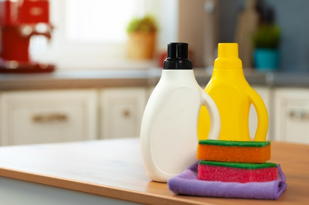 Cleaning detergents and tools on a kitchen counter