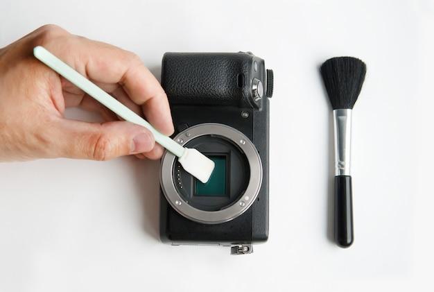 Очистка сенсора цифровой зеркальной камеры тампоном. рука человека, держащая швабру, очищающая пыль от беззеркальной интеллектуальной камеры матричной системы.