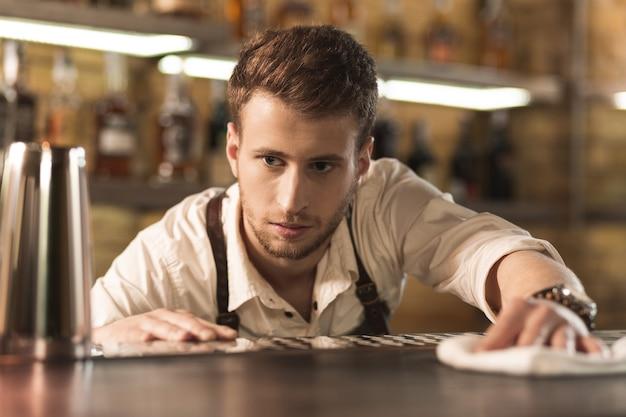 부지런히 청소하십시오. 바텐더로 일하고 부지런히 천으로 바 카운터를 청소하는 잘 생긴 젊은 남자