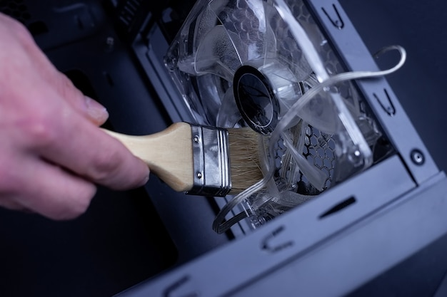 Cleaning dirty desktop computer processor fan from dust by special brush close up