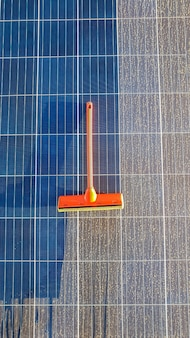Cleaning dirty solar panel at sunset