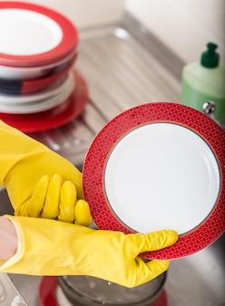 食器洗浄キッチンスポンジ洗浄皿。黄色の保護ゴム手袋洗浄で女性の手のクローズアップ