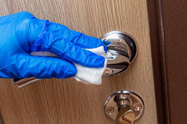 Чистка, дезинфекция, протирание хромированной дверной ручки рукой в перчатке и салфетка крупным планом