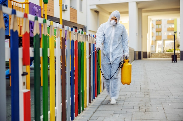 Cleaning and disinfection outside around kindergarten, the covid-19 epidemic. sessional teams for disinfection efforts. infection prevention and control of epidemic. e suit and mask.