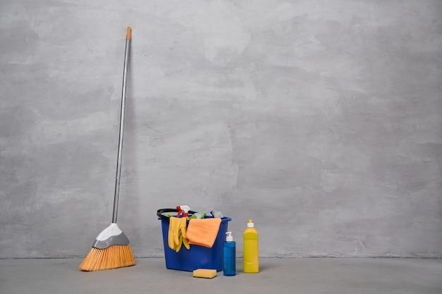 Чистящее оборудование. метла и пластиковое ведро или корзина с моющими средствами, бутылки с моющими средствами, стоящие на полу у серой стены. работа по дому, уборка, концепция домашнего хозяйства