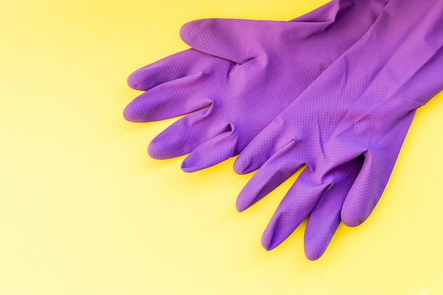 Cleaning equipment isolated on a yellow wall, purple rubber gloves, cleaning tool. the concept of cleaning, protective rubber gloves . hygiene prevention cleaning.
