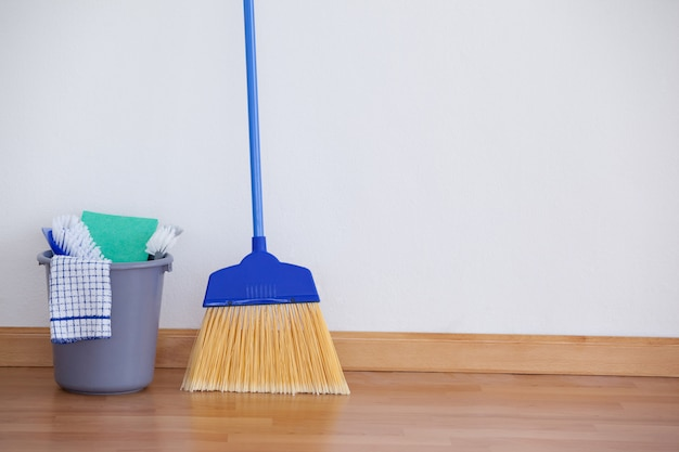 Cleaning equipment on wooden floor against wall
