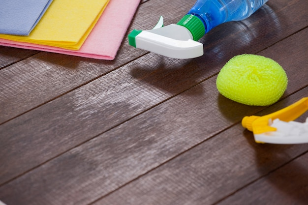 Cleaning equipments arranged on wooden floor background