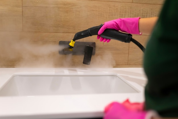 Cleaning the faucet with steam cleaner.
