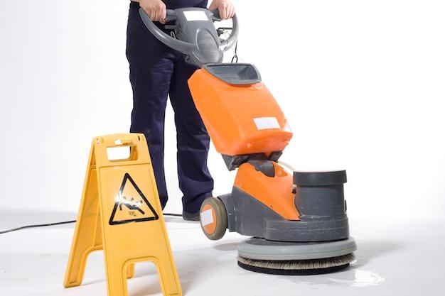 機械で床を掃除する