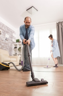 Cleaning floor with vacuum cleaner used by husband