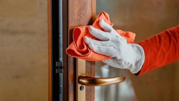 Очистка ручки входной двери антибактериальным спиртовым средством. женщина-домработница в белых перчатках чистит дверную ручку тряпкой. новый нормальный коронавирус covid 19 в дезинфекции поверхностей. длинный веб-баннер