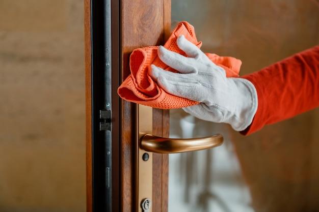 Очистка ручки входной двери антибактериальным спиртовым средством. женщина-домработница в белых перчатках чистит дверную ручку тряпкой. новый нормальный коронавирус covid 19 в дезинфекции поверхностей.