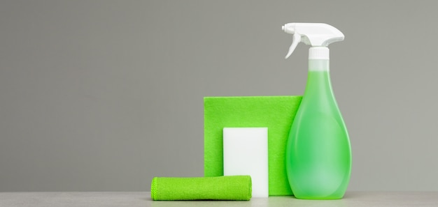 Cleaning green spray bottle with plastic dispenser, sponge and cloth for dust on grey