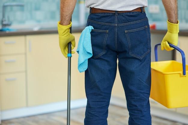 청소 전문가는 플라스틱 양동이를 들고 장갑을 끼고 전문 남성 청소기의 샷을 자른다.