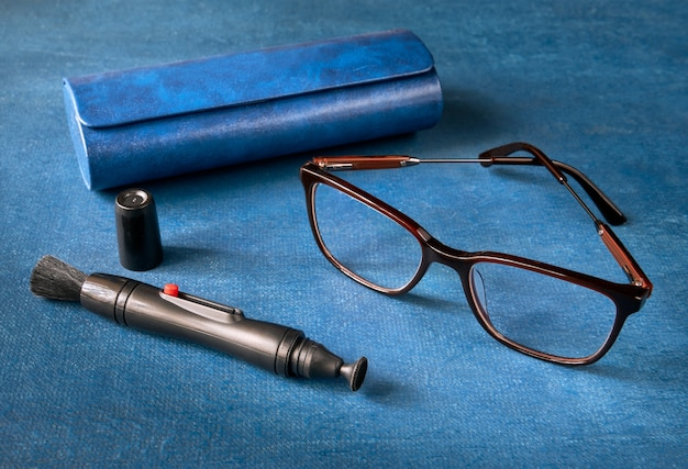 Cleaning handle for lenses, glasses and glasses case on blue space