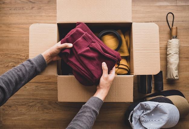 Концепция чистки дома и пожертвования при молодой человек кладя одежду аксессуаров в коробку.