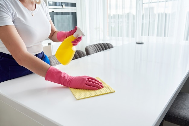 Cleaning home table sanitizing kitchen table surface with disinfectant spray bottle washing surfaces with towel and gloves. covid-19 prevention sanitizing inside.