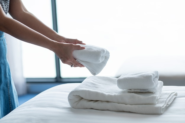 Cleaning hotel, bath towel on white bed, room service