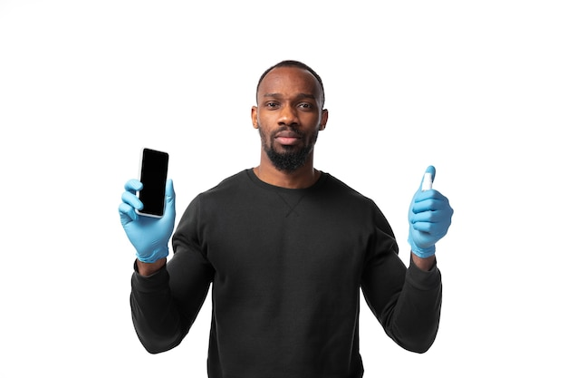 Cleaning. how coronavirus changed our lives. man disinfecting gadgets on white wall. prevention against pneumonia, keep on being on quarantine, stay home. treatment covid, recovering.