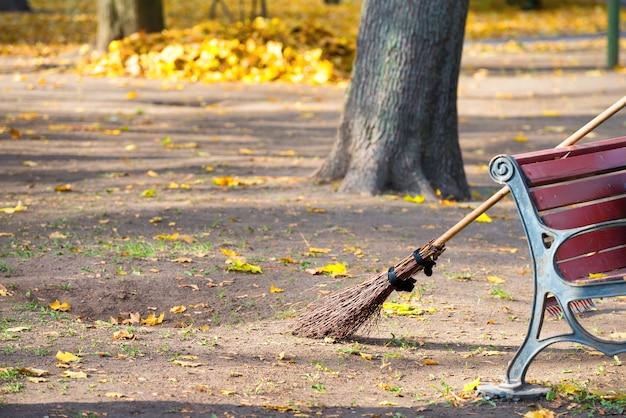 秋の公園での掃除-黄色い落ち葉の山のあるほうきとベンチ