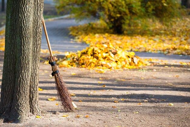 秋の公園での掃除-黄色い落ち葉の山のあるほうき