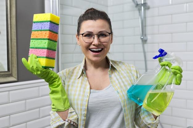 Уборка в ванной. женщина, уборка дома в ванной комнате, держа в руках моющие средства и губки