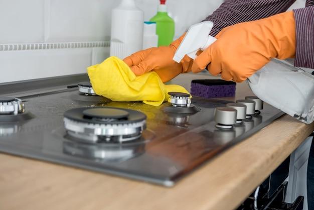 台所のガス石を泡とスポンジで掃除します。健康ライフスタイルのための家庭用機器