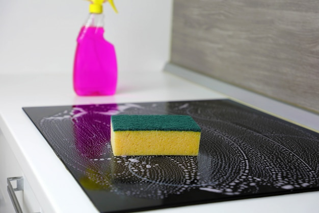Cleaning the induction hob with a sponge.