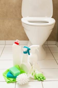 Чистящие средства, перчатки, щетка, белый унитаз для ванной