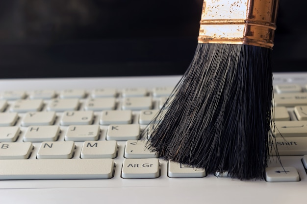 Cleaning keyboard from dust by black brush.