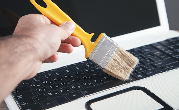 Cleaning the keyboard from dust and dirt with a brush.
