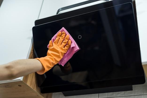 キッチンの掃除。スポンジで台所のフードを洗う女性の手。家事