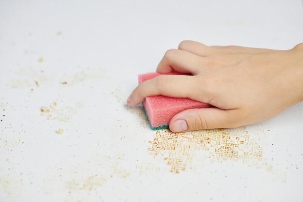 キッチンテーブルの掃除。女性の手のピンクのスポンジは、汚れ、パン粉、残り物を取り除きます。家事