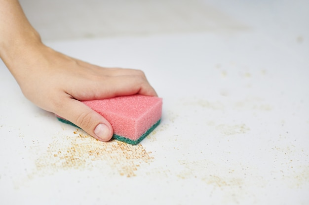 Cleaning kitchen table. pink sponge in woman hand removes dirt, bread crumbs and leftovers. household chores