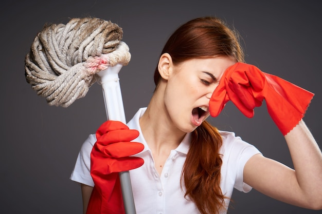 Cleaning lady covers her nose with her fingers unpleasant smell mop in hand