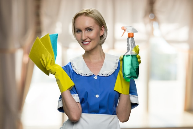 Cleaning lady is holding rags and detergent for cleaning