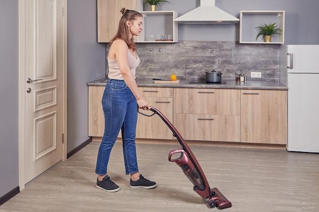 청소부 아줌마는 전기 빗자루를 사용하여 부엌 바닥을 청소하고 있습니다.