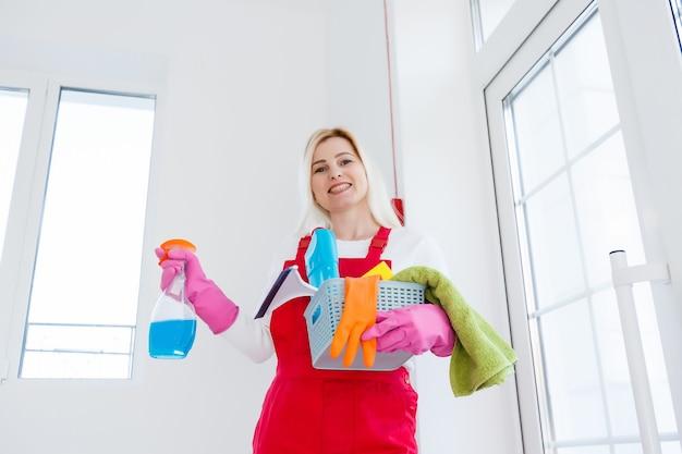 バケツで女性を掃除し、オフィスの背景に製品を掃除します。