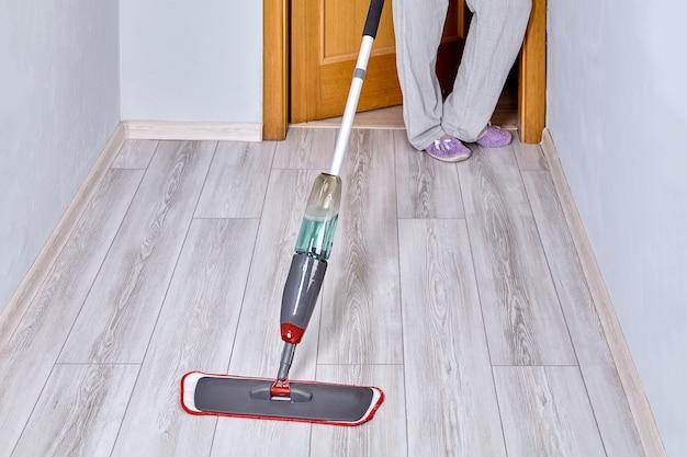 청소부가 먼지와 흙에서 스프레이와 극세사 헤드로 평평한 걸레를 사용하여 라미네이트 바닥을 청소합니다.